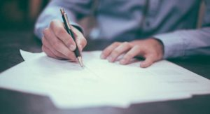 man signing legal papers
