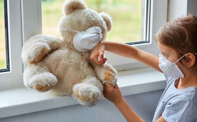 Girl with mask puts sanitizer on masked teddy bear